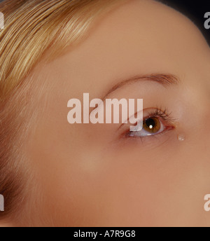 indoors studio woman young girl 20 25 blonde fragment face eye cry tear teardrop sadness sorrow worry close up vertical - Stock Photo