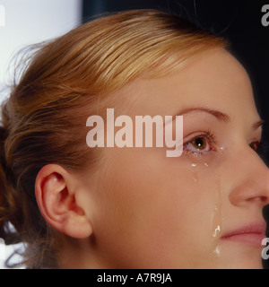 indoors studio woman young girl 20 25 blonde fragment face eye eyes cry flow tear tears teardrop teardrops sadness - Stock Photo