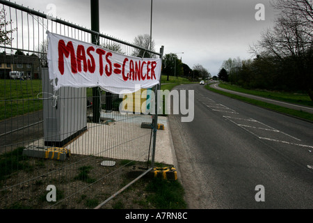 Mobile phone mast with banners attached from protesters in nearby homes and houses close by - Stock Photo