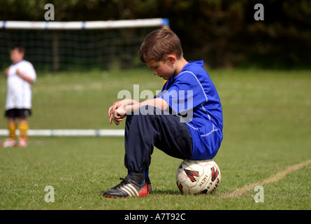 Lonely young boy sitting on football on pitch alone - Stock Photo