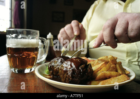 A traditional Black Country meal of faggots and chips served at the Wheatsheaf pub in West Bromwich UK - Stock Photo