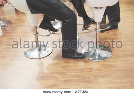 Low section view of two businessmen sitting on chairs - Stock Photo