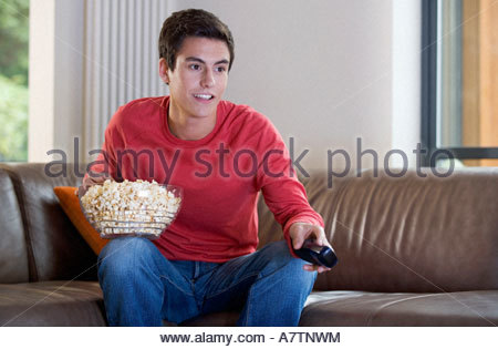 A teenage boy watching television and eating popcorn - Stock Photo