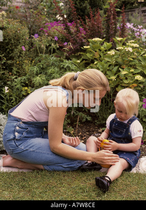 Mother applying suncream to a childs leg in the garden - Stock Photo