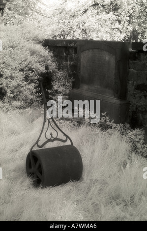 Grainy infrared image of an old fashioned lawn roller abandoned in a graveyard - Stock Photo
