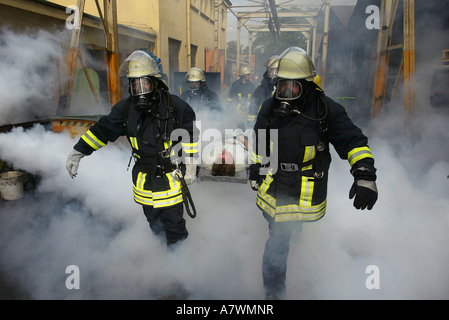 Fire fighters rescue a man during an exercice practice - Stock Photo