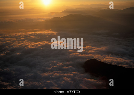 Asia, Nepal, Pokhara, Foothills of Annapurna Massif in the Himalayan Mountains emerge through low clouds at sunset - Stock Photo