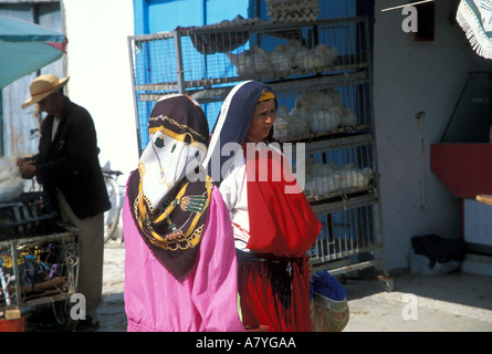 Two colourfully dressed women outside a market in Kairouan Tunisia - Stock Photo