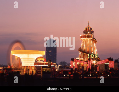 London Hyde Park special event fairground at dusk with tower block of Knightsbridge Army barracks distant - Stock Photo