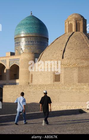 Boys Walking Past Mir-i-Arab Medressa - Stock Photo