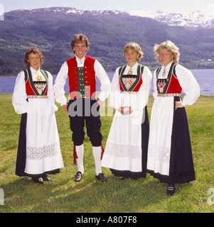 Group wearing traditional Norwegian folk costume with three girls in long black skirts & snow covered mountains - Stock Photo