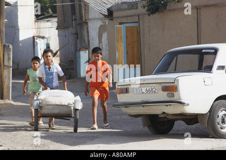 Boys Pushing Cart Through Streets Of Chorsu - Stock Photo