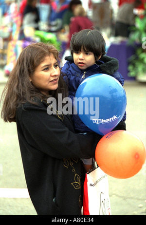 Woman 20 with child age 2 and balloons at Cinco de Mayo. St Paul Minnesota USA - Stock Photo