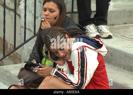 Girls age 16 talking on cell phones and smoking  at Cinco de Mayo Festival. St Paul Minnesota USA - Stock Photo