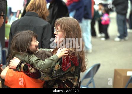 Woman age 40 smiling at girl age 5 at Cinco de Mayo. St Paul Minnesota USA