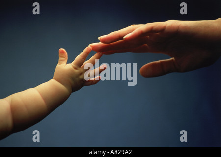 Mother and child reaching for each other love touching tenderness - Stock Photo