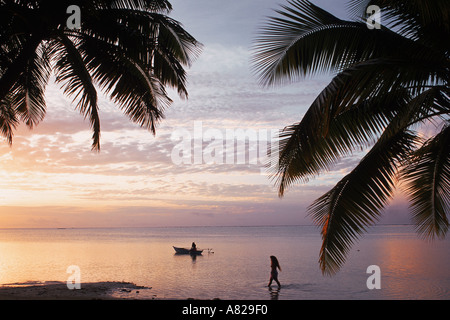 One women walking and one paddling outrigger canoe on Aitutaki Island in Cook Islands