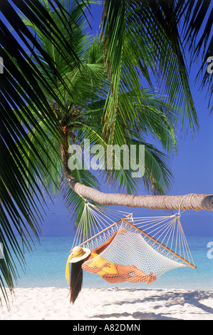 Woman with hat and yellow bathing suit relaxing in hammock under green palms over white sandy beach - Stock Photo
