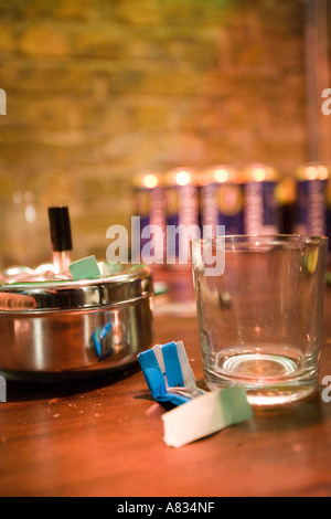 Still life with a glass, a lunchbox, paper and other objects placed on a table against a blurred background - Stock Photo