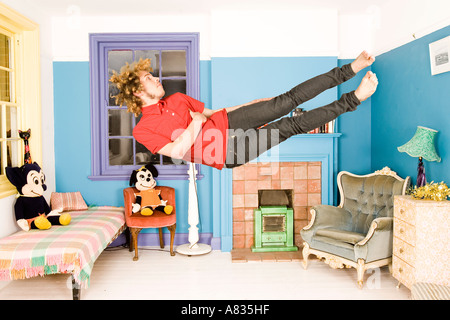 An airborne man in tight dress falling horizontally in a colourfully painted  room with stuffed toys. - Stock Photo