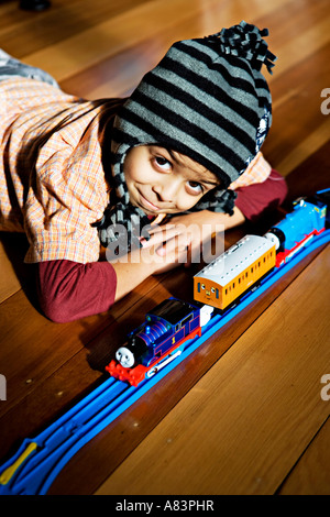 Boy aged 5 years old wears hat and lies on polished wooden floor in sun with toy train set - Stock Photo