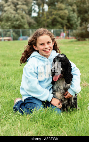 Girl with cocker spaniel dog sitting on grass - Stock Photo