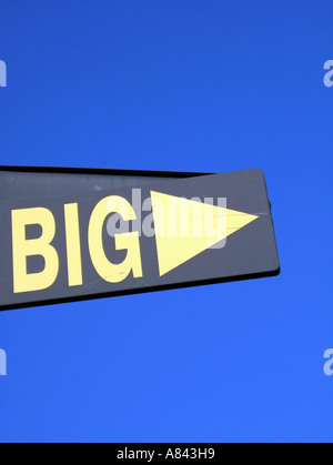 big and arrow sign with blue sky - Stock Photo
