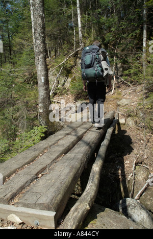 Appalachian Trail- A hiker heading nouth on the AT crosses a wooden foot bridge in New Hampshire USA - Stock Photo