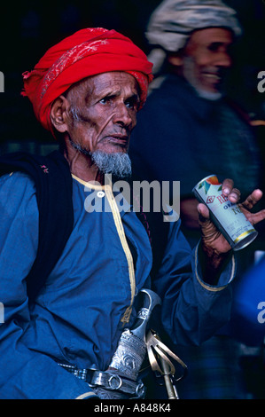 Oman. Town of Taqah in the south. Old soldier Ali Dablan al-Mashadi getting a cool drink. Note  traditional Omani - Stock Photo