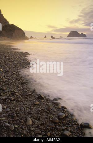 Surf over beach pebbles Oceanside Oregon - Stock Photo