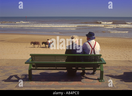 Old couple sitting on bench looking out towards the beach and promenade at Mablethorpe in Lincolnshire England UK Stock Photo