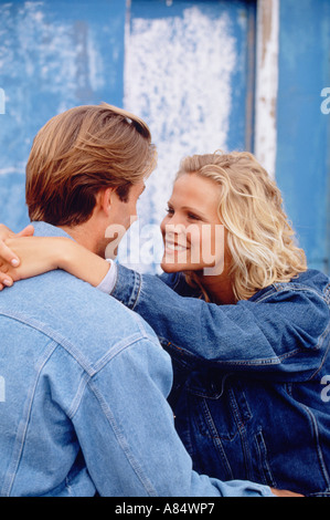 Young couple outdoors sitting on quayside. - Stock Photo