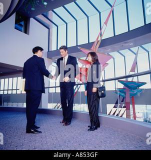 Two men and woman standing on indoor mezzanine floor of modern commercial building. Handshake greeting. - Stock Photo