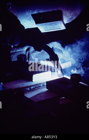United Kingdom. Ship building industry. Close-up of man in protective mask arc welding steel sections. - Stock Photo