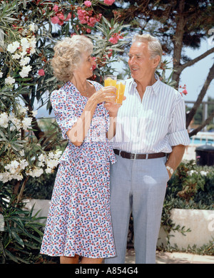 Retirement age couple on vacation, standing with glasses of orange juice on outdoor terrace. - Stock Photo