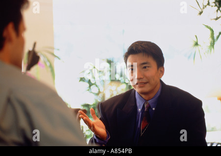 Close-up of Chinese business executive man talking with a European man on restaurant  terrace. - Stock Photo