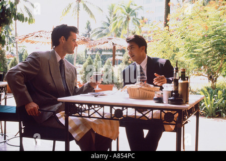 Two men sitting at table in outdoor cafe. - Stock Photo