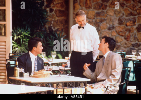 Two men seated at outdoor restaurant table conversing with waiter. Singapore. - Stock Photo