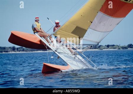 Australia. Two men sailing catamaran yacht tipping on one hull. - Stock Photo