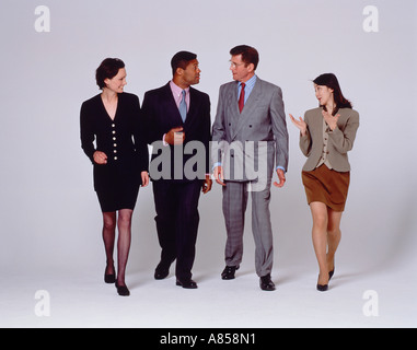 Indoor studio full length image of four walking people talking to each other. - Stock Photo