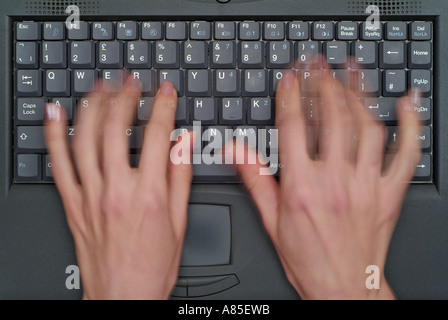Blurred Motion of a Womans Fingers as She Types on the Keyboard of a Laptop Mobile Computer - Stock Photo