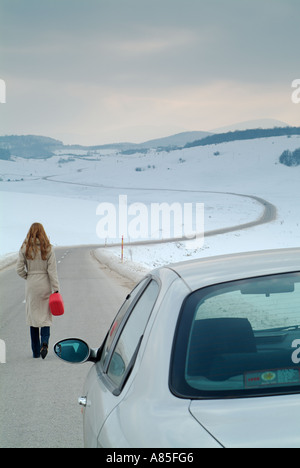 Woman Starts the Long Walk Along an Isolated Country Road in Winter to Find Fuel for Her Broken Down Car - Stock Photo