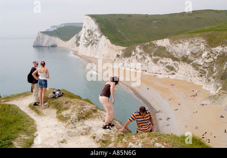 Holidaymakers on footpath enjoy views over limestone cliffs of Bats Head and Swyre Head on the Dorset coast England UK