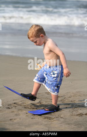 Two year old boy walking with flippers at the beach - Stock Photo