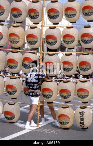 Lantern poles weighing up to 60 kilograms are balanced during Akita's Kanto Matsuri festival - Stock Photo