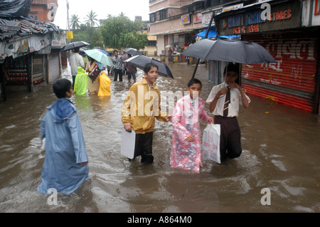 Indian school children on flooded street in record monsoon heavy rainfall day in Bombay Mumbai city India - Stock Photo