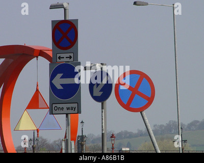 confusing direction arrows and road warning signs stock