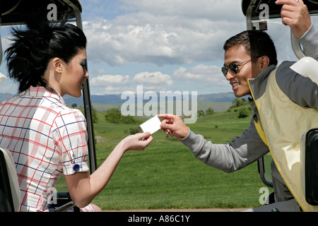 Man passing a woman a card from a golf cart - Stock Photo