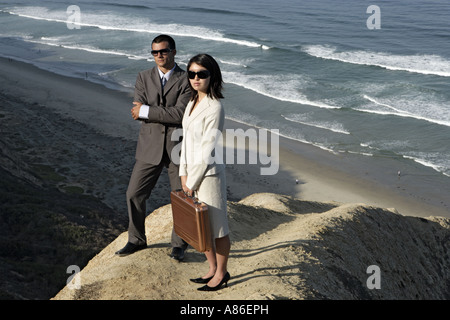 View of a man and a woman standing on a cliff. - Stock Photo