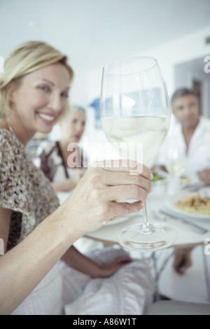 Women holding up a wine glass among a group - Stock Photo